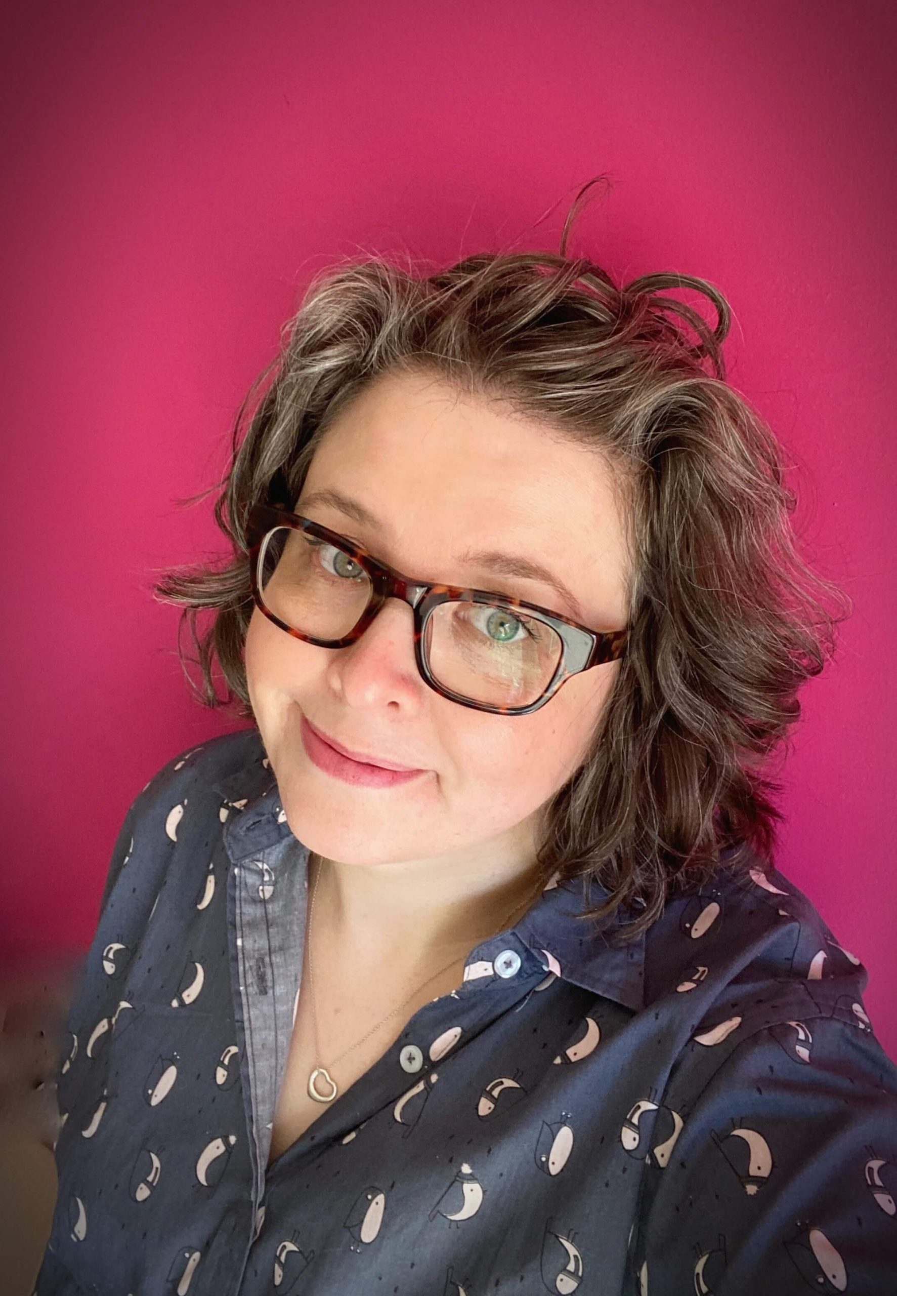 M.J. standing in front of a pink wall. She is smiling, her hair is short and wavy and she's wearing tortoiseshell chunky glasses anda  navy shirt with pink cartoon robins